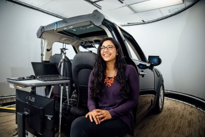 Kiran Bagalkotkar sitting on the tailgate of a driving simulation car.